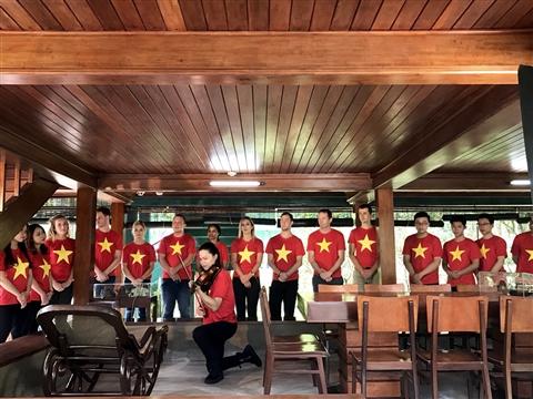 Các bạn trẻ quốc tế khoác trên mình chiếc áo cờ đỏ sao vàng của Tổ quốc Việt Nam, lặng mình đến viếng thăm Chủ tịch Hồ Chí Minh.