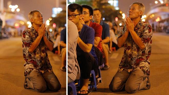 Người đàn ông quỳ dưới đường nhựa trong lễ Vu lan chùa Phúc Khánh